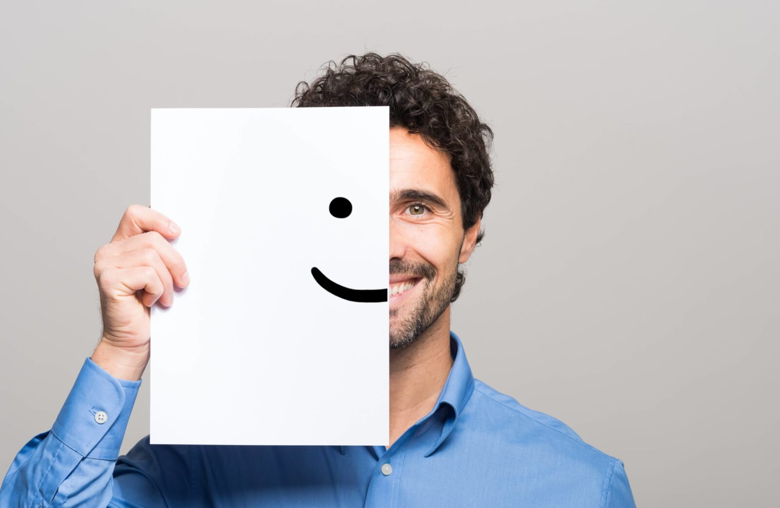 Man Holding a Smiley Face on Paper in Front of his Face