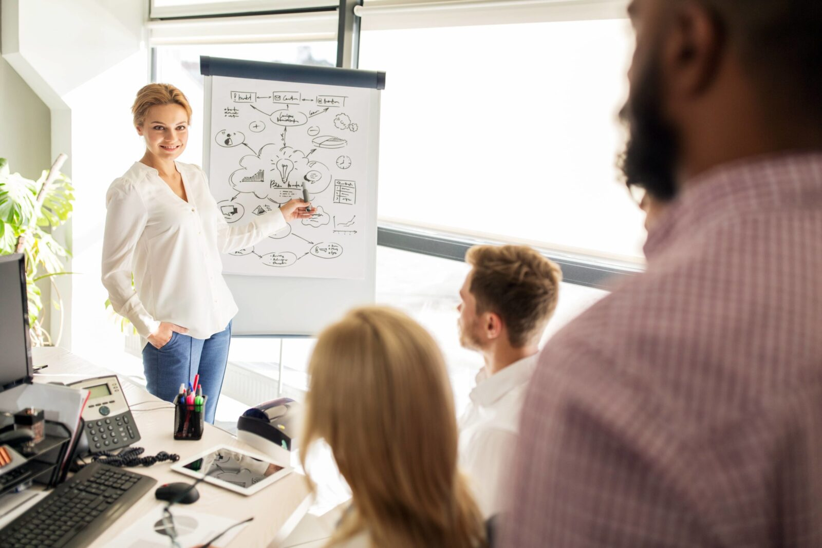Woman Presenting in Front of a Whiteboard